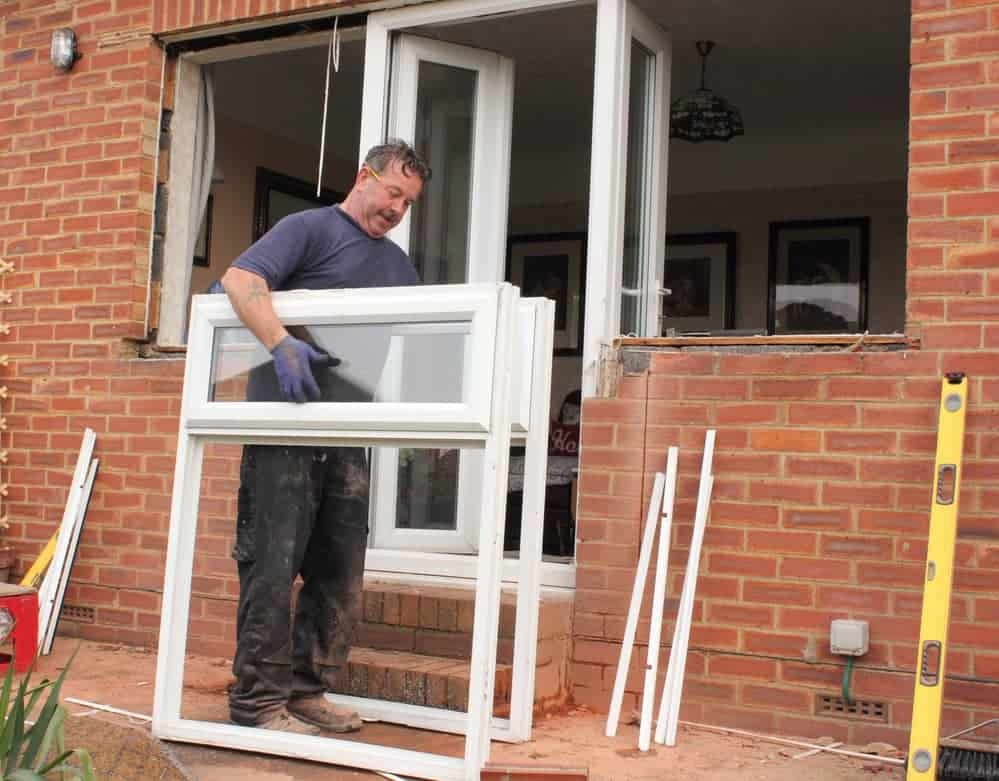 man replacing and installing a window